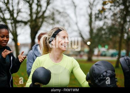 Female boxers wearing boxing gloves training in park - Stock Photo