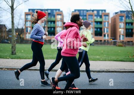 Five female runners running along city sidewalk - Stock Photo