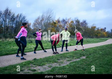 Six adult female runners warming up together on park path - Stock Photo