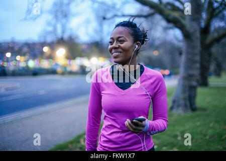 Young woman in exercise clothes, wearing earphones - Stock Photo