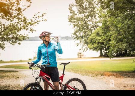 Mature mountain biking woman drinking water at lakeside - Stock Photo