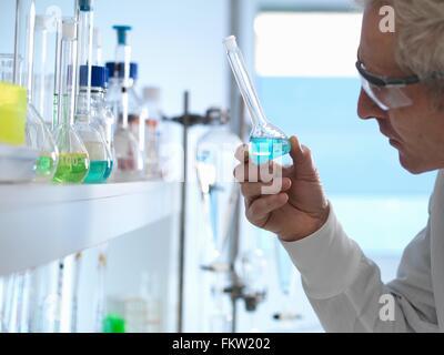 Chemist preparing chemical formula for testing in laboratory - Stock Photo