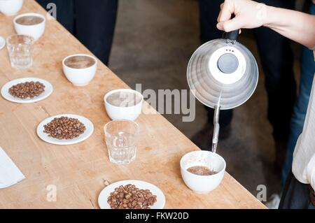 C fee seller pouring hot water into cup   c fee - Stock Photo