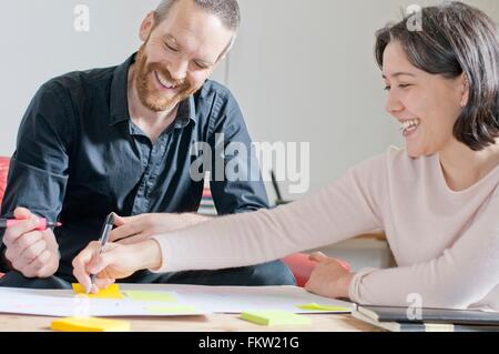 Man and woman laughing in meeting - Stock Photo