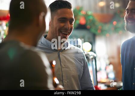 Young man in public house with friends smiling - Stock Photo