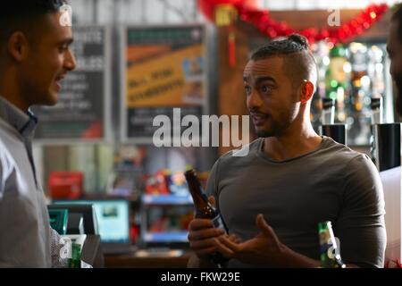 Young man in public house holding beer bottle talking to friend - Stock Photo