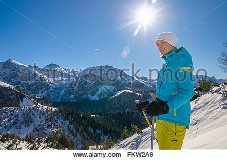 Mid adult woman on mountain top holding walking poles looking away smiling, Jenner, Berchtesgadener, Germany - Stock Photo