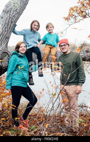Portrait of family, children sitting on tree - Stock Photo