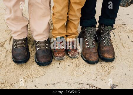 Father standing with two children, focus on feet - Stock Photo