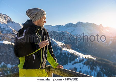 Mid adult man on mountain wearing ski suit and knit hat looking away at view smiling, Jenner, Berchtesgadener, Germany - Stock Photo