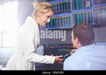 Side view of young business woman in office having discussion with colleague - Stock Photo