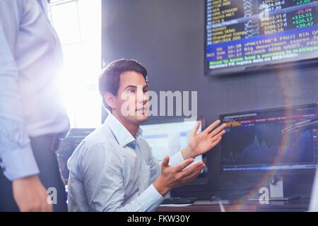 Mid adult business man in office having discussion, hand gestures - Stock Photo