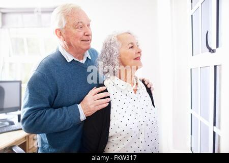 Senior couple in office looking out of window smiling - Stock Photo
