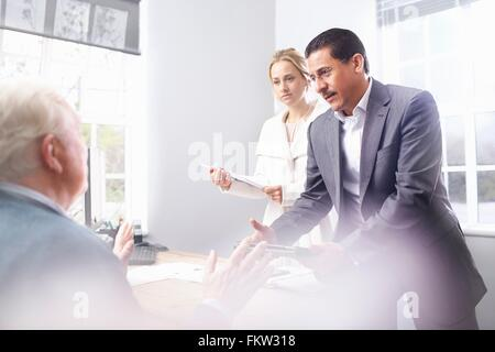 Business man and business woman in office having discussion with senior customer - Stock Photo