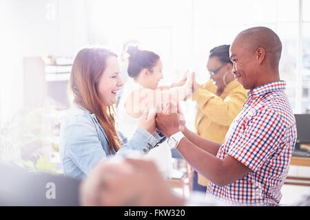 Side view   colleagues in team building task, face to face, hands together smiling - Stock Photo