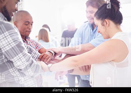 Side view   colleagues in team building task holding wrists smiling - Stock Photo
