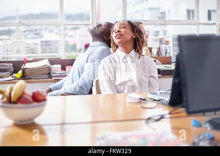 Colleagues in team building task sitting back to back looking away - Stock Photo