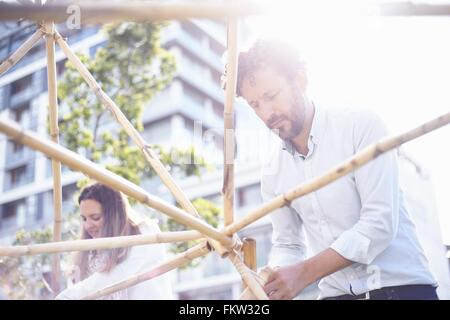Low angle view   mature man in team building task building wooden structure smiling - Stock Photo