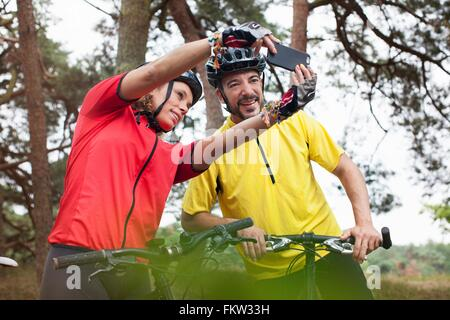 Happy mountain biking couple taking smartphone selfie in forest - Stock Photo