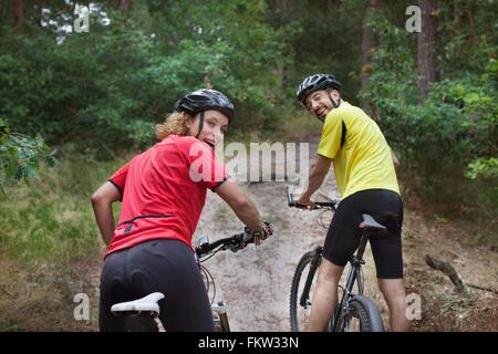 Portrait   mountain biking couple looking over their shoulders in forest - Stock Photo
