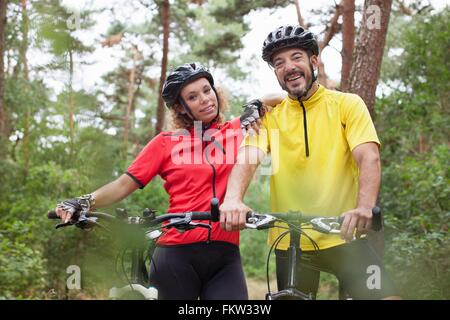 Portrait   happy mountain biking couple in forest - Stock Photo