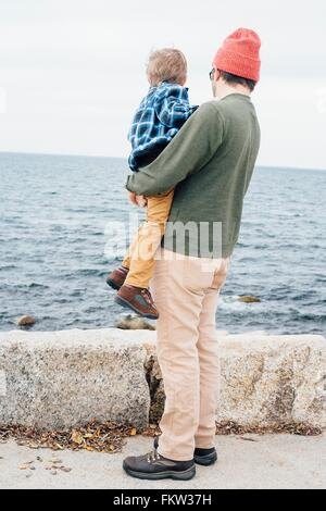 Father holding son beside lake, rear view - Stock Photo