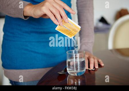 Young woman mixing water-soluble medication from sachet, in glass of water - Stock Photo