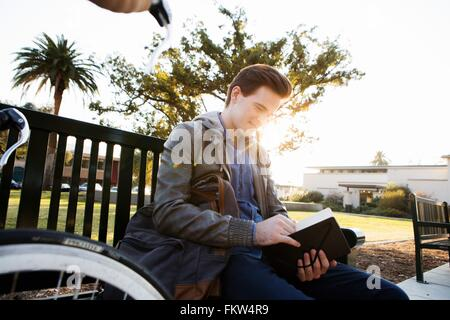 Young man reading book on sunlit park bench - Stock Photo