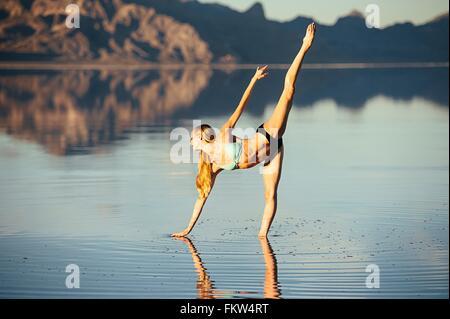 Female ballet dancer poised in ballet position in lake, Bonneville Salt Flats, Utah, USA - Stock Photo