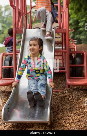 Girl and friends sliding on playground slide - Stock Photo