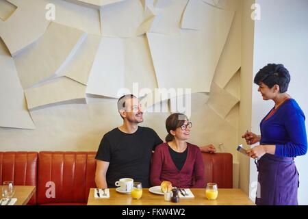 Waitress taking order in restaurant from mid adult couple - Stock Photo