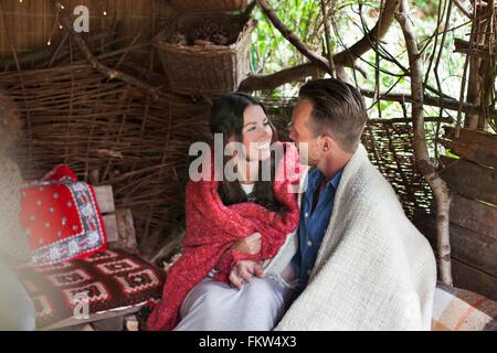 Romantic couple wrapped in blankets in cabin - Stock Photo