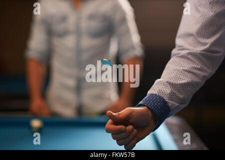 Man tossing coin at pool table - Stock Photo