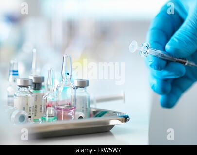 Doctor placing syringe back onto tray with drug vials - Stock Photo