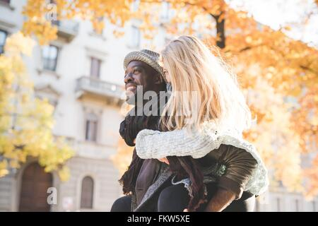 Man giving woman piggyback ride - Stock Photo