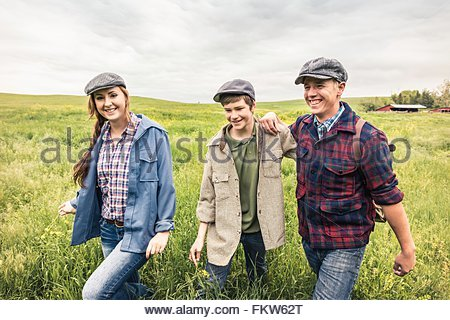 Young adults and teen boy wearing flat caps walking in tall grass looking at camera smiling - Stock Photo