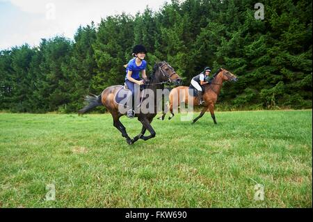 Side view of girl and mature woman wearing riding hats galloping on horseback - Stock Photo