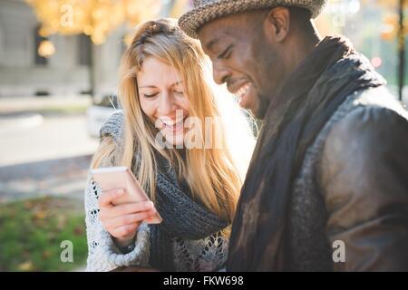Couple using smartphone - Stock Photo