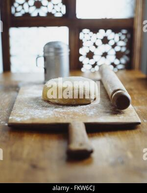 Dough, rolling pin on wooden chopping board, making bread - Stock Photo
