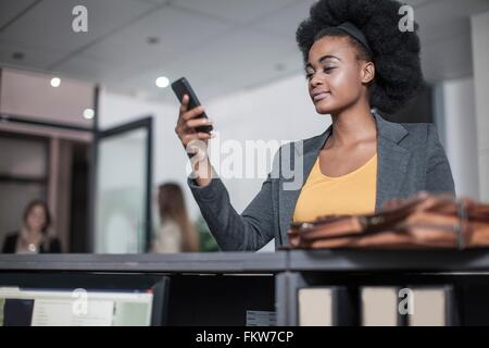Young businesswoman reading smartphone text at office reception - Stock Photo