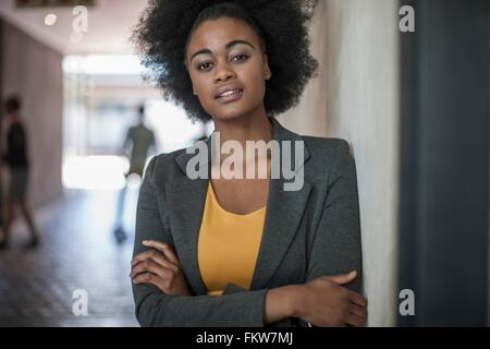 Portrait of confident young businesswomen leaning against office wall - Stock Photo