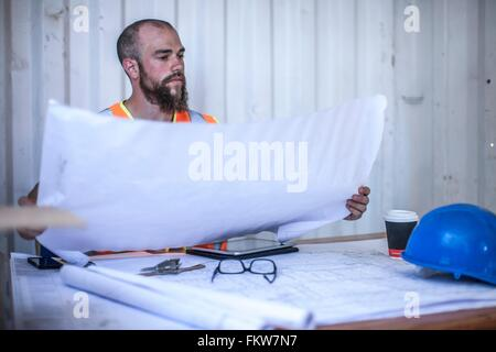 Construction worker sitting at desk looking at blueprint in portable cabin - Stock Photo