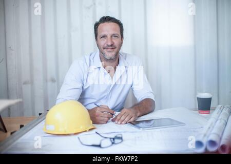 Portrait of male construction foreman at desk in portable cabin - Stock Photo