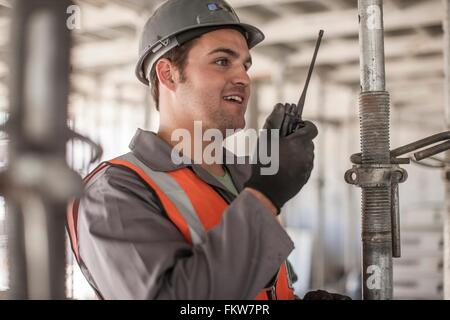 Builder using walkie talkie on construction site - Stock Photo