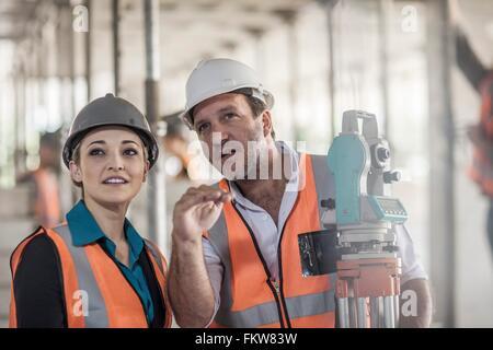 Surveyor explaining to female builder on construction site - Stock Photo