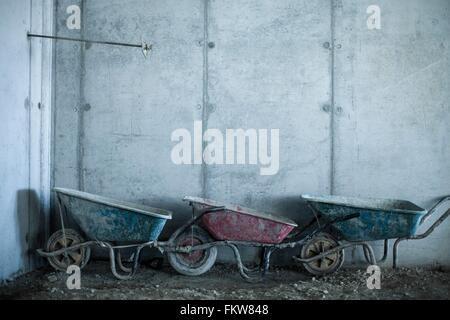 Row of three wheelbarrows on construction site - Stock Photo