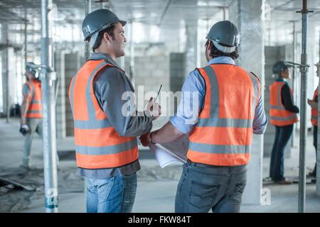 Rear view of site manager and  builder meeting with blueprint on construction site - Stock Photo