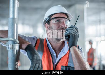 Mid adult male site manager using walkie talkie on construction site - Stock Photo