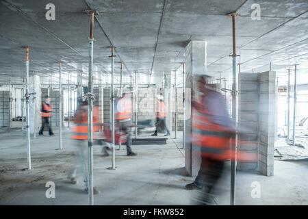 Six blurred construction workers on the go in busy construction site - Stock Photo