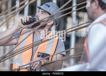 Site manager using walkie talkie on  construction site - Stock Photo